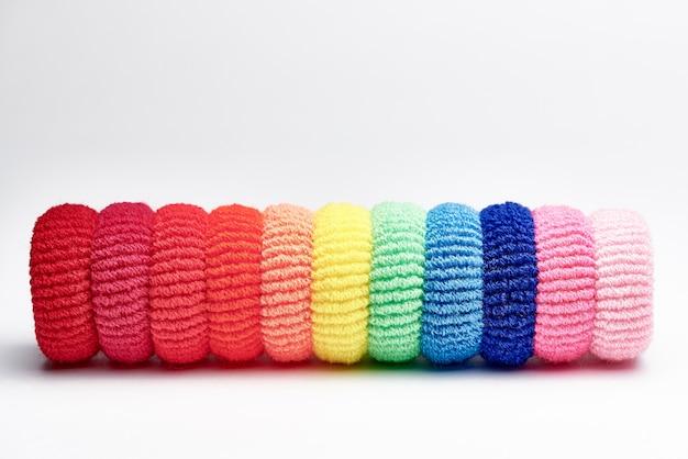 Eine reihe heller mehrfarbiger haargummis. helle mehrfarbige gummibänder für haare.