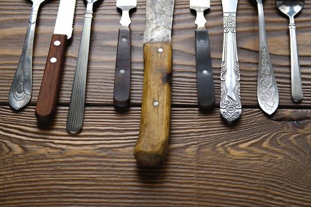 Eine reihe verschiedener vintage-bestecke mit messern, gabeln und löffeln