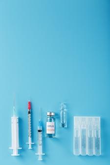 Eine reihe von ampullen und spritzen mit dem inschriftenvirus-impfstoff und eine reihe von spritzen