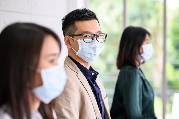 Eine reihe von asiaten trägt aus sicherheitsgründen gesichtsschutzmasken