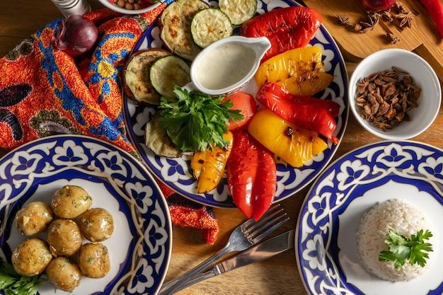 Eine reihe von beilagen. gegrilltes gemüse, gekochter reis und ofenkartoffeln in traditionellen usbekischen gerichten.