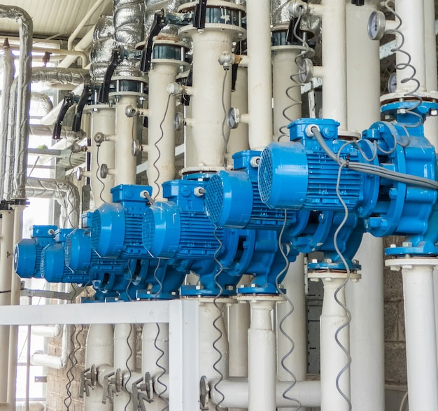 Eine reihe von blauen elektrischen wasserpumpen. schläuche und motoren in der industrie