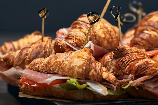 Eine reihe von croissants und sandwiches mit verschiedenen füllungen, käse, parmaschinken, mozzarella und tomaten. fast-food-patern.