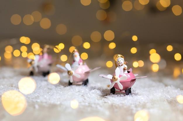 Eine reihe von dekorativen weihnachten-themen-statuetten. weihnachtsmann-rotwild und schneemann in den rosafarbenen flugzeugen mit propeller.