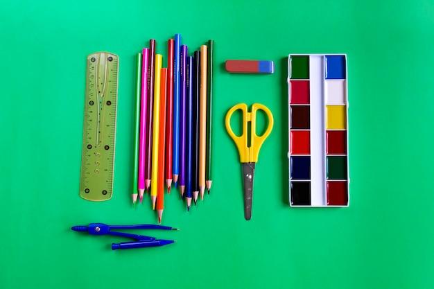 Eine reihe von farben, stiften, scheren, lineal, radiergummi und kompasse auf grün