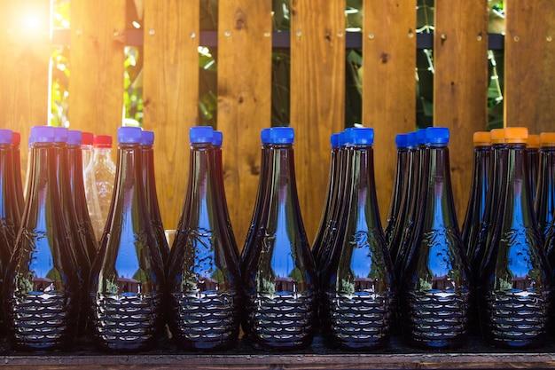 Eine reihe von flaschen mit hausgemachtem wein auf einem tisch