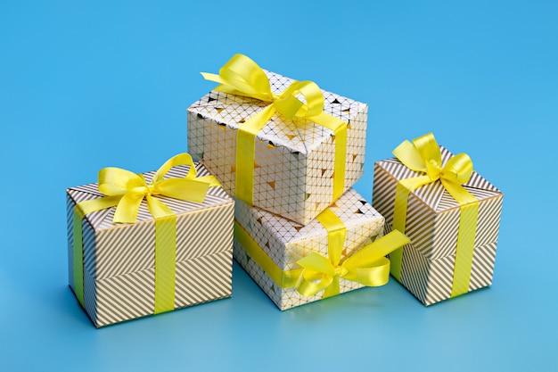 Eine reihe von geschenkboxen in einer eleganten verpackung mit bändern und schleifen. blauer hintergrund, kopierraum.