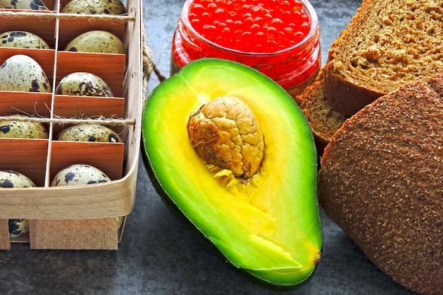 Eine reihe von gesunden produkten für die ketodiät. öko-produkte. wachteleier, avocados, kleiebrot, roter kaviar.