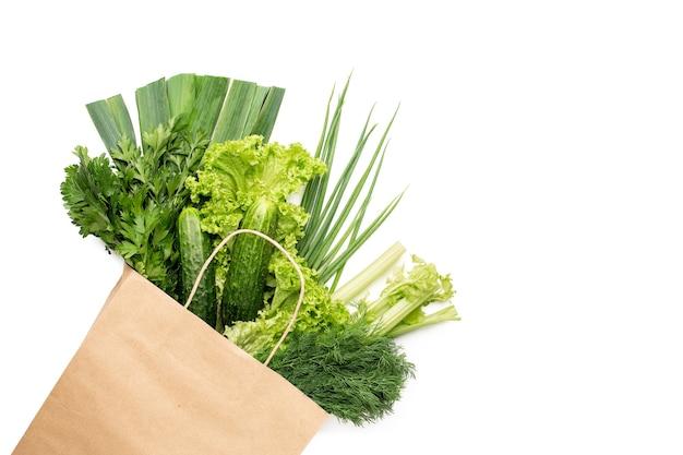 Eine reihe von grünen produkten in einer papiertüte. isoliert auf weißem hintergrund. einkaufen in einem supermarkt oder markt.