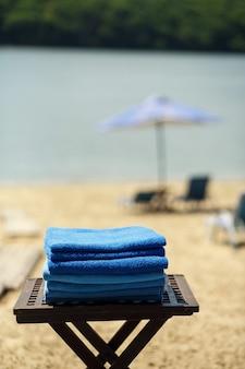 Eine reihe von handtüchern auf dem tisch am strand.