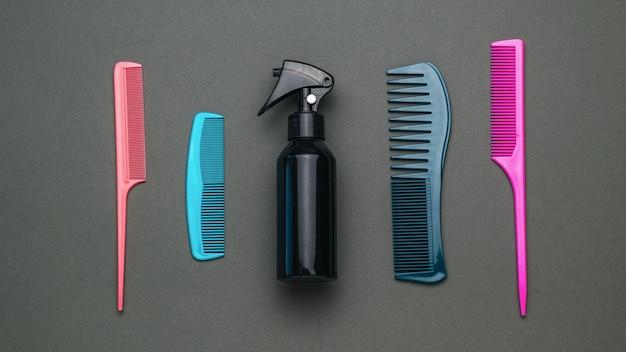 Eine reihe von kämmen und haarspray auf dunkelgrauem hintergrund. ein werkzeug für die haarpflege. flach liegen.