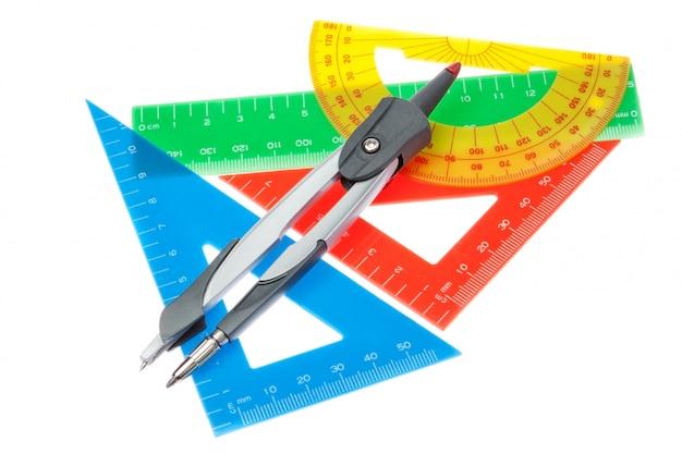 Eine reihe von linealen für die schule und ein kompass an einer weißen wand.