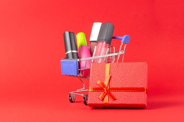 Eine reihe von lippenstiftkosmetik und lipgloss, puder, lidschatten und ein einkaufswagen auf leuchtend rotem hintergrund. das konzept des kaufs von kosmetika, online-shopping, urlaub