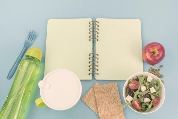 Eine reihe von nützlichen produkten, kirschtomaten, apfel obst samen plastikgeschirr weiße blumen frischer salat