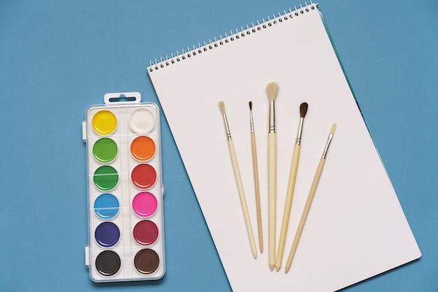 Eine reihe von pinseln, ein skizzenbuch und helle aquarelle auf blauem hintergrund das konzept der kreativität