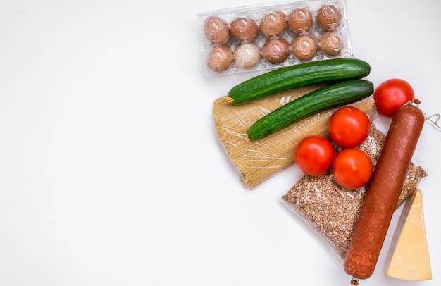 Eine reihe von produkten auf einem weißen hintergrund. lebensmittel, gemüse, butter, eier und wurst. lebensmittelpaket
