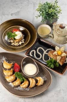 Eine reihe von schönen desserts und eine tasse grüner tee mit einer teekanne. süße gyoza-knödel mit frischen erdbeeren, mandeltarte mit eis und gebratener esterhazy-kuchen mit physalis und minze