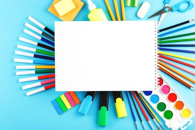 Eine reihe von schulmaterial für das lernen und die kreative entwicklung auf einem blauen hintergrund. freier speicherplatz auf dem weißen album, der blick von oben Premium Fotos
