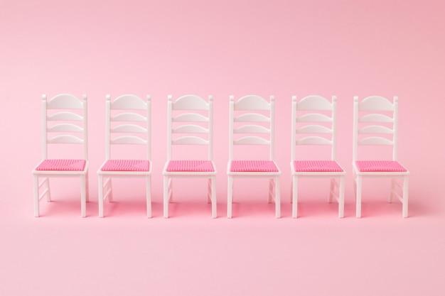 Eine reihe von sechs stühlen auf einer rosa oberfläche