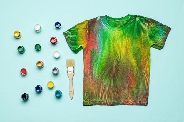 Eine reihe von stofffarben und ein stylisches tie-dye-t-shirt auf blauem hintergrund. flach liegen.