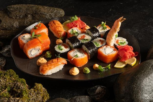 Eine reihe von sushi auf einem schönen schwarzen teller. japanisches gericht. sushi-rollen mit chuka-salat und lachs, philadelphia maki mit frischkäse, sashimi, garnelen.