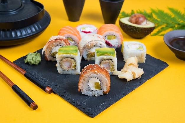 Eine reihe von sushi-rollen anderer art auf einem gelben raum. draufsicht. traditionelles asiatisches essen
