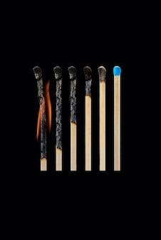 Eine reihe von verbrannten streichhölzern von vollständig verbrannt bis ganz isoliert auf einem schwarzen hintergrund