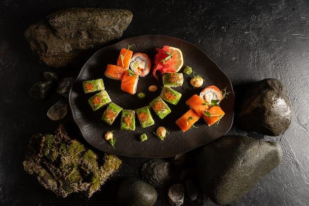 Eine reihe von verschiedenen arten von sushi auf einem schönen schwarzen teller. japanisches gericht.
