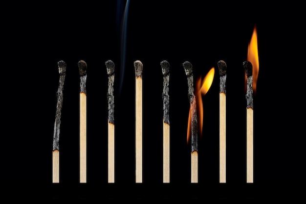 Eine reihe von verschiedenen verbrannten streichhölzern mit rauch mit unterschiedlichem feuer lokalisiert auf einem schwarzen hintergrund