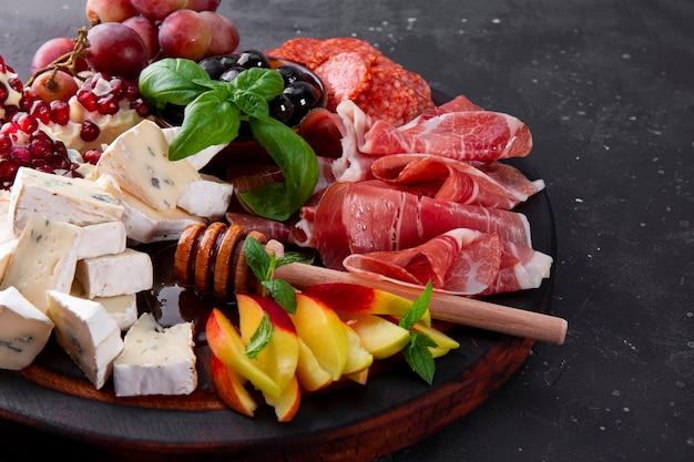 Eine reihe von vorspeisen für wein jamon peperoni-käse-trauben pfirsich und oliven auf einem holzbrett