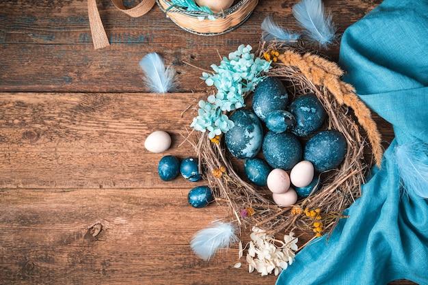 Eine reihe von wachtel- und hühnereiern in dunkelblauen und pastellfarbenen farben in einem wunderschönen nest mit blumen und