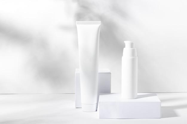 Eine reihe von weißen kosmetikgläsern auf quadratischen ständen mit schatten. zahnpasta, gesichts- und körpercreme, haarshampoo. professionelle kosmetik für die hautpflege. bio-kosmetik.