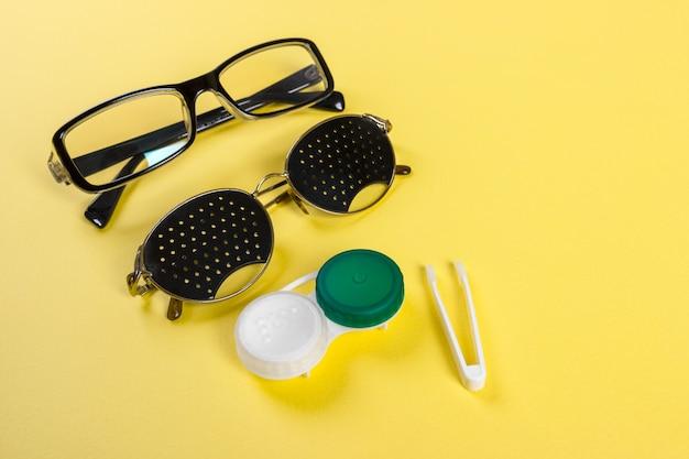 Eine reihe von zubehör für den anblick. lochbrillengläser, linsen mit behälter und gläser zum sehen. paar medizinische lochbrillen mit reflexionen.