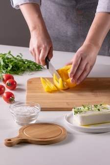 Eine reihe von zutaten käse, tomaten, rucola, salz für einen gesunden salat. hand eines mädchens, das einen pfeffer auf einem holzbrett auf einem weißen küchentisch schneidet. schritt-für-schritt-foto