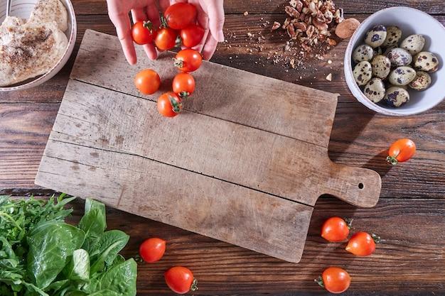Eine reihe von zutaten wachteleier, frische kräuter, nüsse, gekochtes fleisch auf einem holztisch. die hände des mädchens legten tomaten mit einem kopierraum auf das küchenbrett. diät-salat kochen. flach liegen