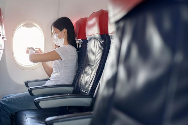 Eine reisende frau, die schutzmaske an bord im flugzeug mit smartwatch trägt, unter covid-19-pandemie reist, sicherheitsreisen, soziales distanzierungsprotokoll, neues normales reisekonzept