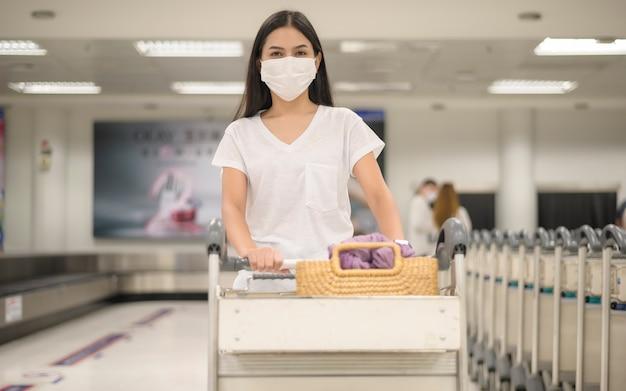 Eine reisende frau, die schutzmaske im flughafen mit gepäck auf wagen, reise unter covid-19-pandemie, sicherheitsreisen, protokoll der sozialen distanzierung, neues normales reisekonzept trägt