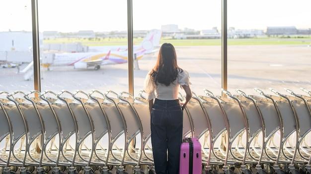 Eine reisende frau trägt eine schutzmaske auf dem internationalen flughafen, reist unter der covid-19-pandemie, sicherheitsreisen, soziales distanzierungsprotokoll