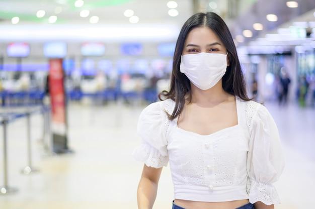Eine reisende frau trägt eine schutzmaske auf dem internationalen flughafen und reist unter der covid-19-pandemie