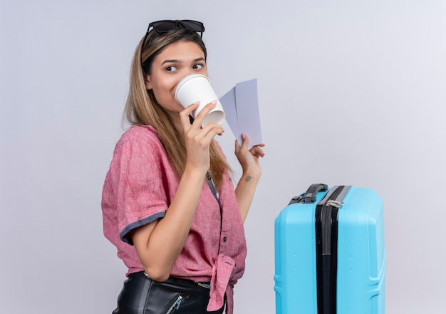 Eine reizende junge frau, die rotes hemd und sonnenbrille trägt, die einen kaffee trinken, während flugtickets an einer weißen wand halten