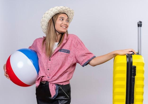 Eine reizende junge frau, die rotes hemd und sonnenhut hält, die aufblasbaren ball hält und hand auf gelben koffer an einer weißen wand legt