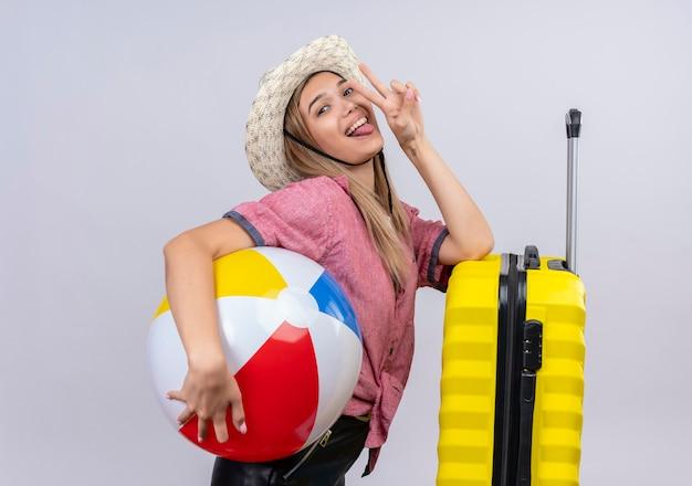 Eine reizende junge frau, die rotes hemd und sonnenhut mit aufblasbarem ball trägt und hand auf gelben koffer legt, während geste mit zwei fingern auf einer weißen wand zeigt