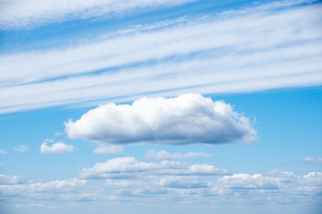Eine riesige cumuluswolke und viele kleine wolken auf einem blauen himmel, naturhintergrund.