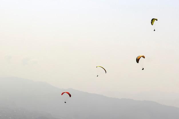 Eine riesige gruppe von sportlern fliegt in einem professionellen anzug auf einem gleitschirm in den himmel.