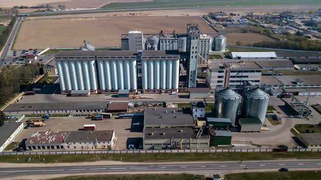 Eine riesige ölraffinerie mit metallkonstruktionen, rohren und destillation des komplexes mit brennenden lichtern in der abenddämmerung. luftaufnahme