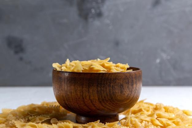 Eine rohe italienische pasta der vorderansicht, die wenig innerhalb des braunen tellers auf dem hellen tischnudelitalienspeisen gebildet wird