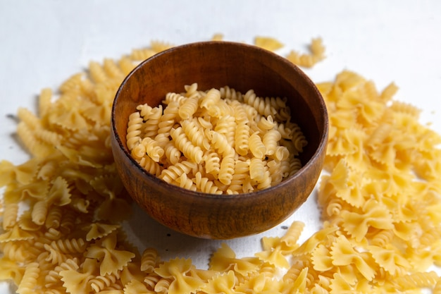 Eine rohe italienische pasta der vorderansicht, die wenig mit braunem teller auf dem hellen tischnudelitalienspeisen gebildet wird