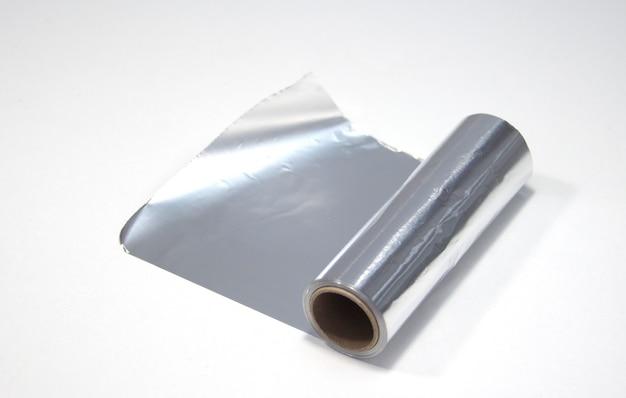 Eine rolle aluminiumfolie auf weißem hintergrund. folie für den friseur
