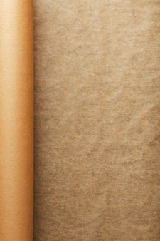 Eine rolle des aufgeklappten braunen pergamentpapiers, für das backen des lebensmittels herein auf einem dunklen hintergrund, draufsicht.