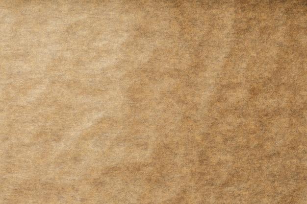 Eine rolle des aufgeklappten braunen pergamentpapiers, für das backen des lebensmittels im hintergrund, draufsicht.